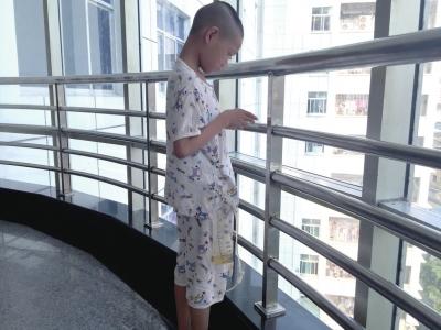 8月1日上午,小宝在张家界市人民医院的走廊里等候治疗。京华时报记者郑羽佳摄