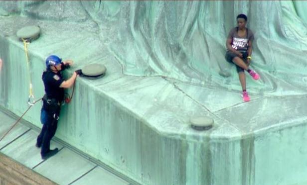反对特朗普移民政策 美国独立日一女子爬上自由女神像基座抗议
