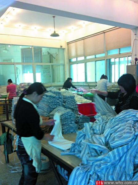 洗衣作坊里叠衣服的女工全都着便服、赤手上阵.