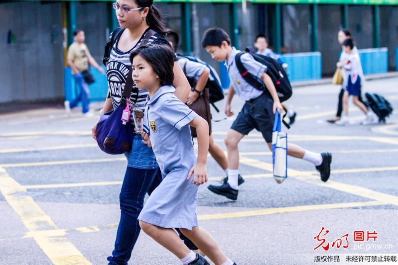 香港:小学生功课负担沉重 家长陪伴上学帮背书包
