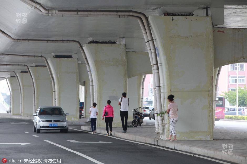 市一快速路高架桥下,排水管用透明胶带固定在桥墩上