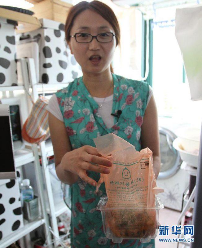 在韩国首尔,主妇金莲心向记者展示她家的食物垃圾袋。新华社记者姚琪琳摄
